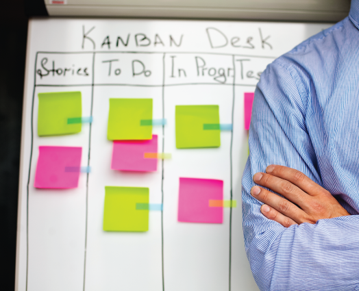IQbusiness - Man in blue and white striped formal shirt with a white board in the background with green and pink sticky notes