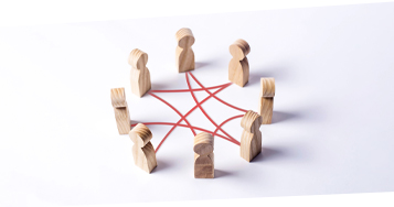 Wooden Human-like figures standing in a circle to symbolize Big Room Planning and scaled agile communication